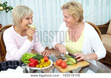 Two mature women making vegetable salad at home