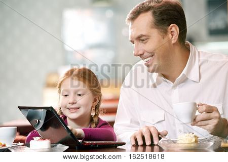 Father and daughter dining at cafe, the girl using computer