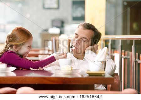 Little girl treating her sleeping father at cafe