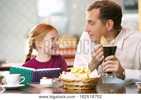 Man communicating with his little daughter at cafe