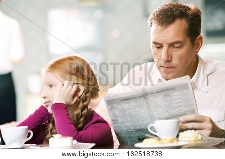 Bored daughter sitting at cafe with her indifferent father
