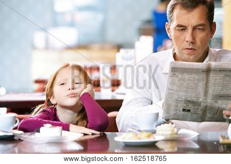 Man reading paper at cafe and his little daughter sitting bored