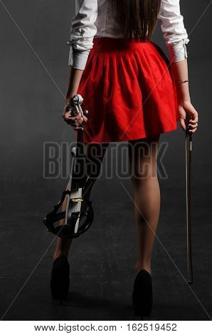 Women's legs in a skirt with a violin. Back view. Vertical photo