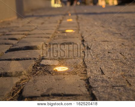 Picture of the cobblestone paved road with spotlight close up. Dark brown cobblestone road pattern close up. Selective focus on the middle of the picture. Spotlights against the blurred background