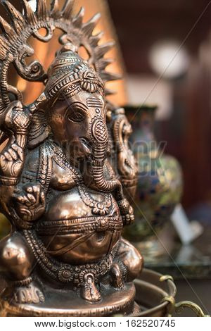 Small metal statuette of Ganesha, the Hindu god with elephant head, in an interior setting