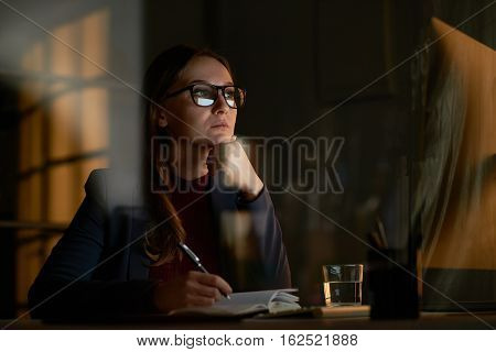 Portrait of concentrated brunette woman in glasses and formal suit working alone in dark office late at night, looking at bright computer screen and making notes in notebook