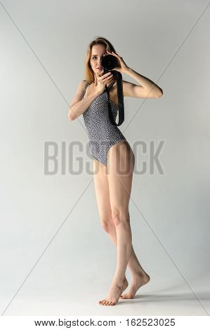 Young beautiful fashionable deplorable model shoots photo by camera over grey background