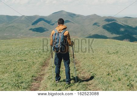 Explorer young man with backpack and trekking poles walking in the mountains