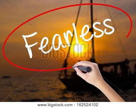 Woman Hand Writing Fearless With A Marker Over Transparent Board.