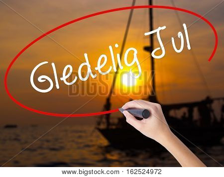 Woman Hand Writing Gledelig Jul  (happy Christmas In Norwegian) With A Marker Over Transparent Board