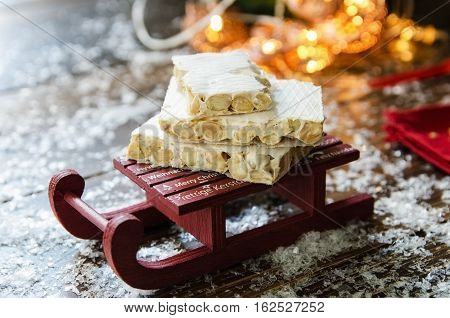 Turron traditional Spanish sweet consumed at Christmas. Almond nougat dessert on decorative sleigh with snow and Christmas tree with garland on the background.