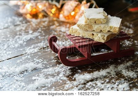 Turron traditional Spanish sweet consumed at Christmas. Almond nougat dessert on decorative sleigh with snow and Christmas tree with garland on the background.Copy space.