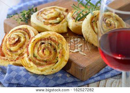 Baked hearty puff pastry rolls with ham, cream cheese, parmesan and herbs; served with a glass of red wine