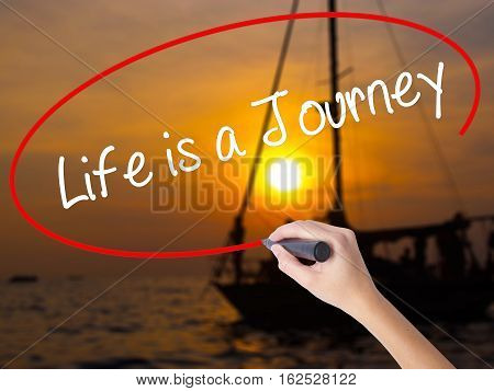 Woman Hand Writing Life Is A Journey With A Marker Over Transparent Board.
