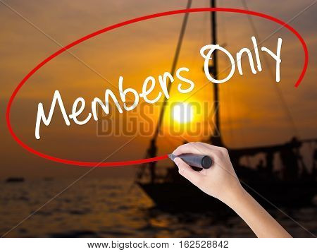 Woman Hand Writing Members Only With A Marker Over Transparent Board.