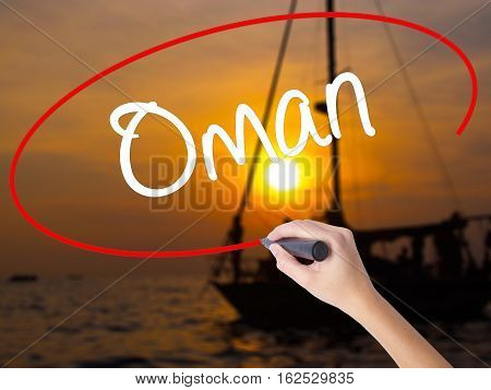Woman Hand Writing Oman   With A Marker Over Transparent Board