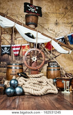 Pirates ship deck with steering wheel and flag.