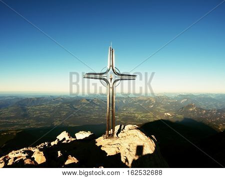 Cross With Semi-precious Stone Raised  At Mountain Summit  In Alps. Sharp Peak