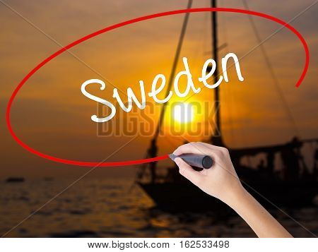Woman Hand Writing Sweden  With A Marker Over Transparent Board