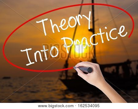 Woman Hand Writing Theory Into Practice With A Marker Over Transparent Board