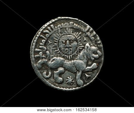Ancient Seljuk Silver Coin With Image Of Sun And Lion Isolated On Black