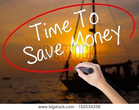 Woman Hand Writing Time To Save Money  With A Marker Over Transparent Board.