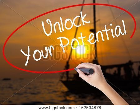 Woman Hand Writing Unlock Your Potential With A Marker Over Transparent Board
