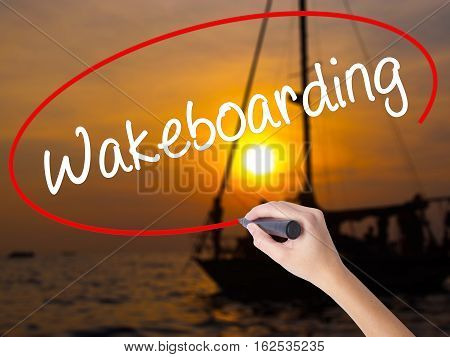 Woman Hand Writing Wakeboarding With A Marker Over Transparent Board.
