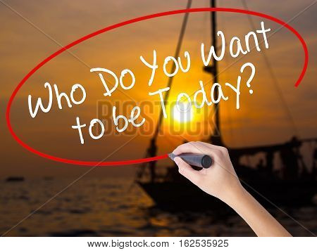 Woman Hand Writing Who Do You Want To Be Today? With A Marker Over Transparent Board.