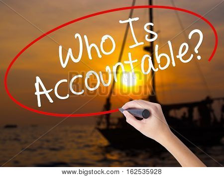 Woman Hand Writing Who Is Accountable? With A Marker Over Transparent Board