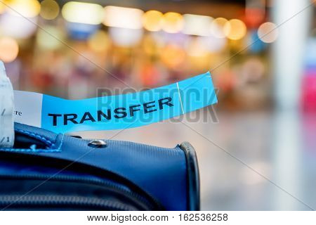 Close-up photograph of luggage with transfer label at airport with blurred background. Problems with transfer. Lost baggage