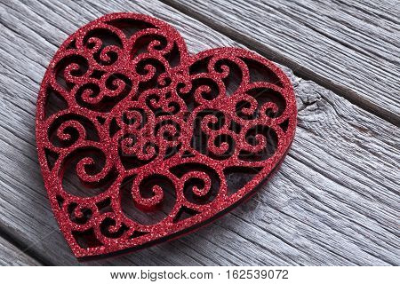 Valentine background with lace red heart shape closeup on rustic wood. Happy lovers day card mockup