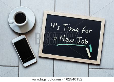 Chalkboard or Blackboard concept saying - IT'S TIME FOR A NEW JOB - with coffee and mobile phone. Business Personal Education Effective Management concept.