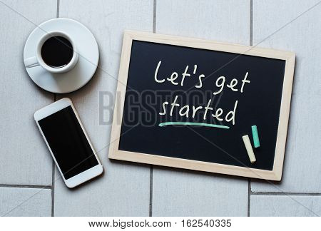 Chalkboard or Blackboard concept saying - LET'S GET STARTED - with coffee and mobile phone. Business Personal Education Effective Management concept.