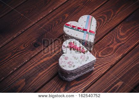 Two handmade caskets or gift boxes in form of heart on dark rustic wooden background. copy space for text. can be used at Valentine's Day
