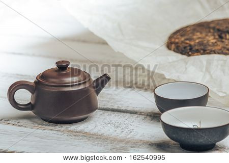 Teapot from Yixing clay for Chinese tea ceremony on rustic wooden background with tea cups and old shu puerh