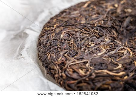 old Shen puerh chinese fermented tea on papyrus paper background macro close-up image