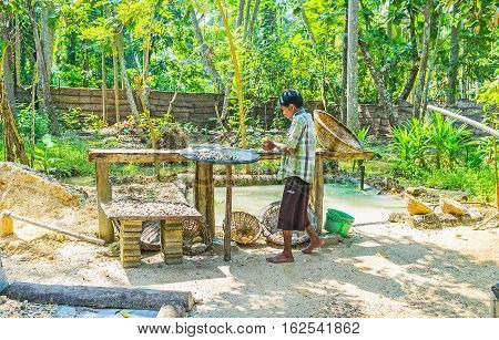 MEETIYAGODA SRI LANKA - DECEMBER 5 2016: The worker of moonstone mine at his working place - washes and filters out the stones on December 5 in Meetiyagoda.