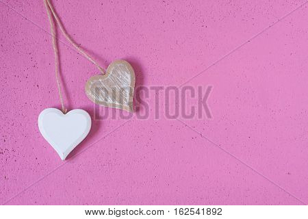 wooden hearts on a pink texture background