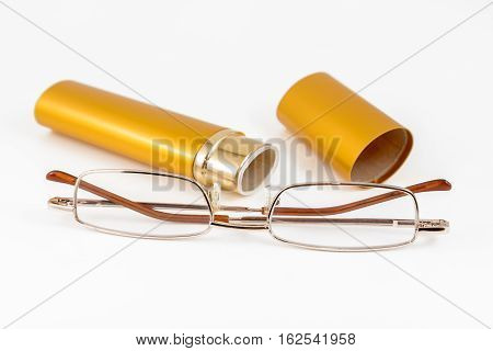 Glasses in gold case shot on white background