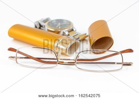 Glasses in gold case and watch shot on white background