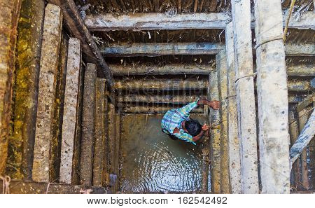 The worker climbs down the moonstone mine shaft filled with muddy water after the rain to extract the gems Meetiyagoda Sri Lanka.