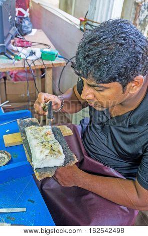 MEETIYAGODA SRI LANKA - DECEMBER 5 2016: The silversmith heats with a burner the base of the jewelry on December 5 in Meetiyagoda.