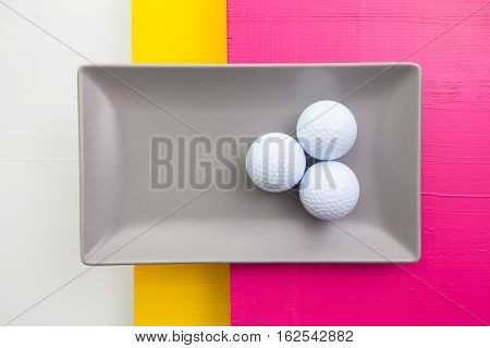 Gray ceramic dish with golf balls on over white yellow and pink wooden table rectangle dish