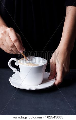 hand holding a cup of coffee, latte coffee on a black background