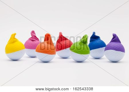 White golf balls with funny caps on the white background. Funny golf concept.