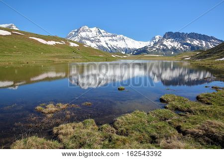 VANOISE, FRANCE: View of four summits (Rechasse, Grande Casse, Grande Motte and Pierre Brune) from a lake in Northern Alps