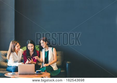 Three beautiful Asian girls using smartphone and laptop chatting on sofa at cafe with copy space modern lifestyle with gadget technology or working woman on casual business concept