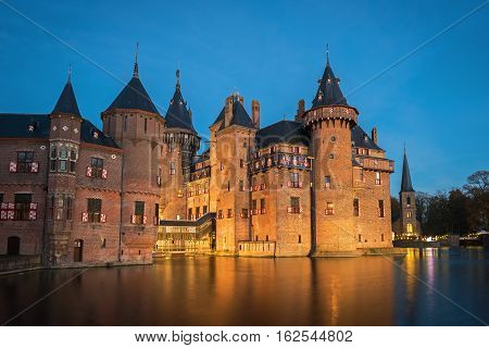 View of the medieval castle  De Haar in the evening illumination, The Netherlands