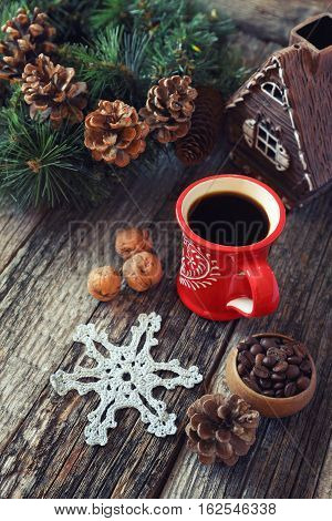 Cup of coffee coffee beans pine cones and New-Year tree decorations on a wooden background. Toned image